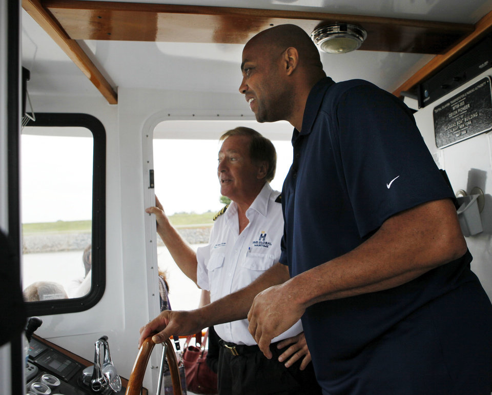 Photo - Charles Barkley takes a turn at the wheel of a Devon river cruiser as Capt. Joe Harvey guides him during a cruise of the Oklahoma River in Oklahoma City, Friday, June 1, 2012. Barkley took the cruise as part of a tour of Oklahoma City. Photo by Nate Billings, The Oklahoman