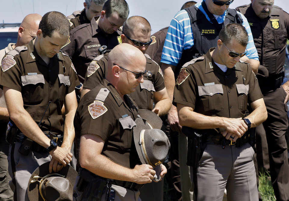Photo - After the suspect had been apprehended, state troopers joined Logan County deputies and other law enforcement officers in bowing their heads and respectfully observing a moment of silence for the slain deputy.  The man accused of fatally shooting a Logan County sheriff's deputy Tuesday, April 18, 2017,  and leading authorities on a manhunt near Langston, is in custody, according to Logan County Sheriff Damon Devereaux.  Authorities identified Nathan Aaron LeForce, 45, as the person who shot Logan County Sheriff's Deputy David Wade while Wade was serving an eviction notice at a home in Mulhall.     Photo by Jim Beckel, The Oklahoman