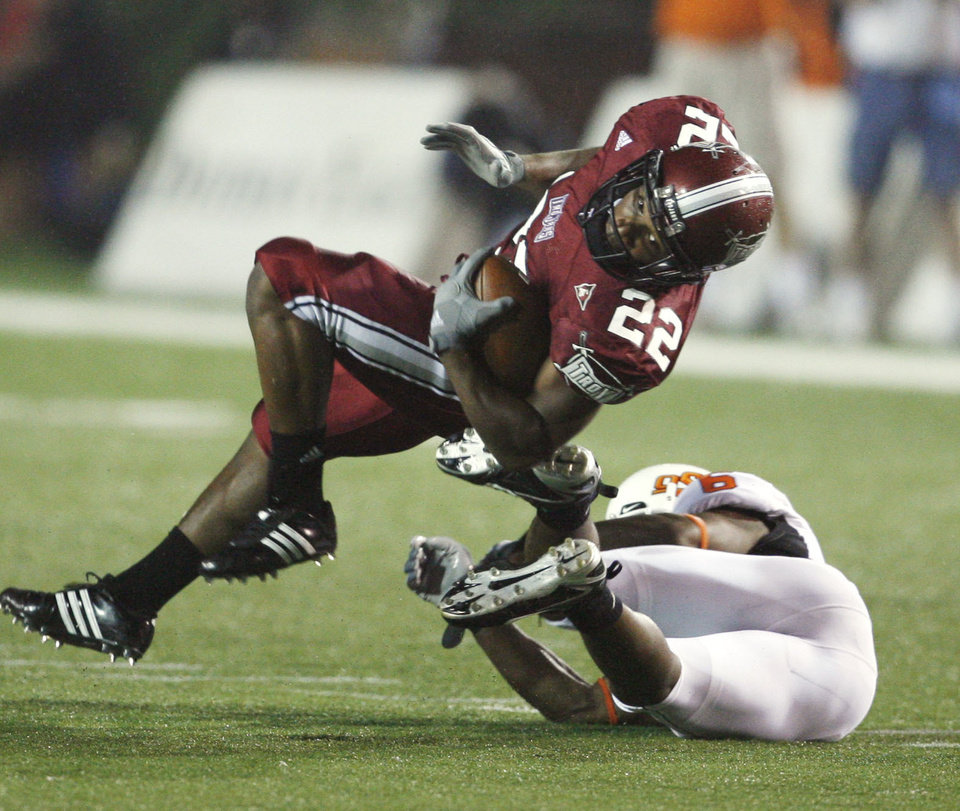 Photo - Kenny Cattouse spins past Ricky Price in first half action during the college football game between the Troy University Trojans and the Oklahoma State University Cowboys at Movie Gallery Veterans Stadium in Troy, Ala., Friday, September 14, 2007. BY STEVE SISNEY, THE OKLAHOMAN
