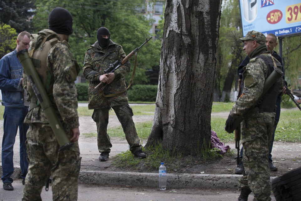 Photo - Pro-Russian gunmen stand with their weapons behind barricades in Slovyansk, eastern Ukraine, Friday, May 2, 2014. Ukraine launched what appeared to be its first major assault against pro-Russian forces who have seized government buildings in the country's east, with fighting breaking out Friday in a city that has become the focus of the insurgency. (AP Photo/Alexander Zemlianichenko)