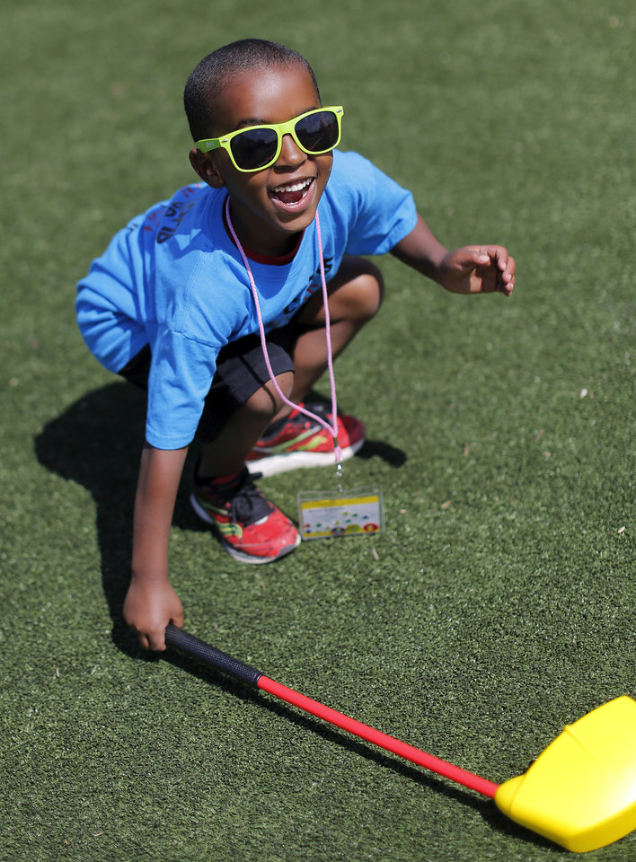 Photo - Metek Crabtree, 6, smiles after hitting a plastic golf ball in the 'Stars of the Future' area north of Boone Pickens Stadium on the campus of Oklahoma State University on Thursday, May 15, 2014. Crabtree was with a group of children from Central's Littlebits.  Special Olympics athletes numbering in the thousands are competing in various events today and tomorrow  in Stillwater as the organization's 45th Annual Summer Games are held in Oklahoma this week.  Officials say more than 4,600 Special Olympics Oklahoma athletes have registered to compete this year, and thousands of volunteers are assisting during the three days of competitions.   This is the 31st year the summer games has been centered at Oklahoma State University.  Special Olympics is the world's largest sports organization for children and adults with intellectual disabilities, providing year-round training and competitions to more than 4.2 million athletes in 170 countries, according to their web site. Photo by Jim Beckel, The Oklahoman