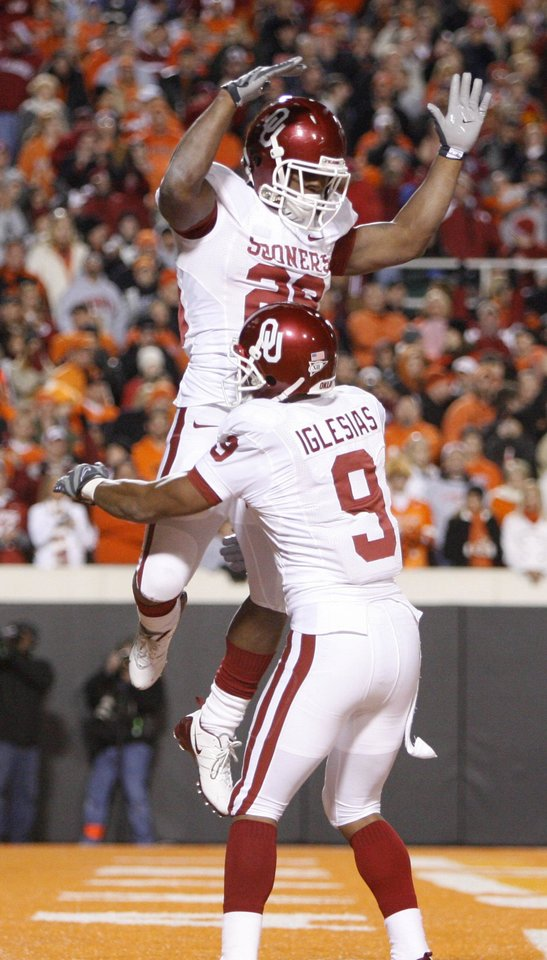Photo - Chris Brown leaps in the arms of Juaquin Iglesias after scoring a touchdown during the first half of the college football game between the University of Oklahoma Sooners (OU) and Oklahoma State University Cowboys (OSU) at Boone Pickens Stadium on Saturday, Nov. 29, 2008, in Stillwater, Okla. STAFF PHOTO BY BRYAN TERRY