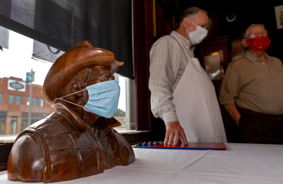 Photo - A cowboy bust and the staff at Cattlemen's Steakhouse wear a mask during the restaurants reopening in Oklahoma City, Okla. on Friday, May 1, 2020. Cattlemen's Steakhouse and other restaurants begin their gradual reopening on Friday after being closed due to the Coronavirus Pandemic.[Chris Landsberger/The Oklahoman]