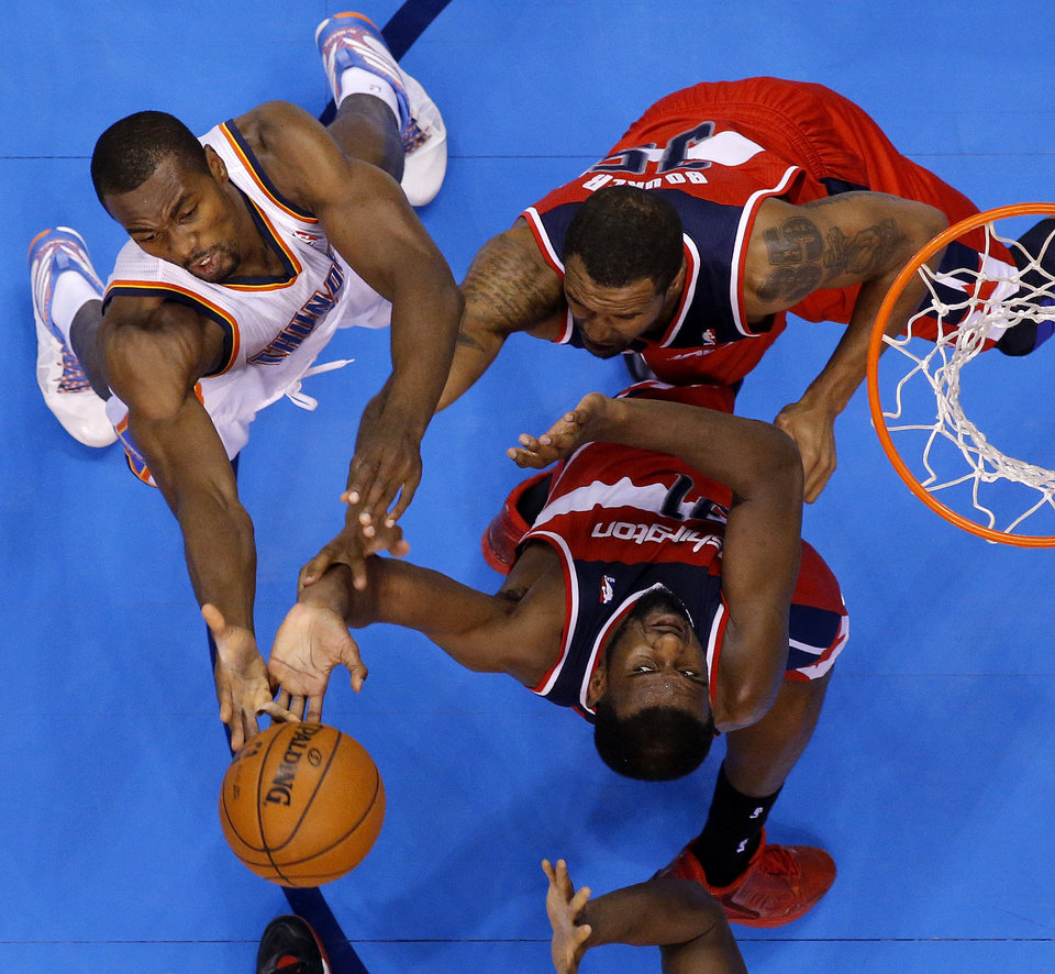 Oklahoma City\'s Serge Ibaka (9) fights for the ball with Washington\'s Trevor Booker (35) and Chris Singleton (31) during an NBA basketball game between the Oklahoma City Thunder and the Washington Wizards at Chesapeake Energy Arena in Oklahoma City, Wednesday, March 19, 2013. Photo by Bryan Terry, The Oklahoman