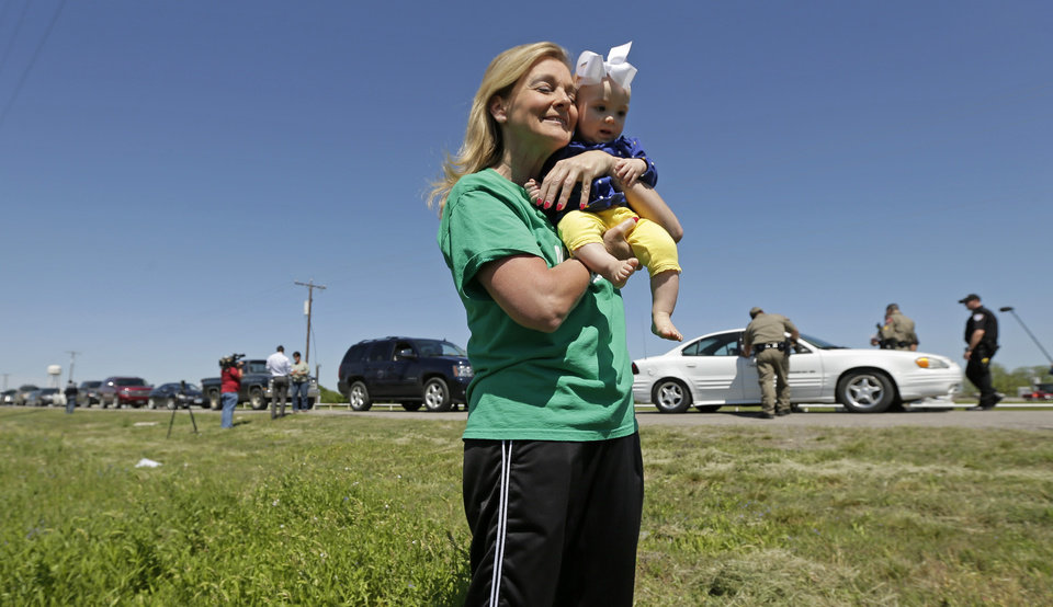 Photo - Displaced resident Debby Keel holds her granddaughter Kennedy Keel as she waits by a checkpoint for residents waiting to go back to their homes Saturday, April 20, 2013, three days after an explosion at a fertilizer plant in West, Texas. The massive explosion at the West Fertilizer Co. Wednesday night killed 14 people and injured more than 160. (AP Photo/Charlie Riedel)