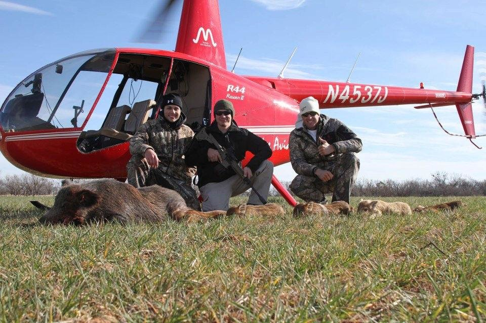 Photo - Eric Lewis and hunter Dustin Ellermann and pilot Dustin Johnson display feral hogs that they shot on a hunt in Texas. Lewis and Johnson are the CEOs of Cedar Ridge Aviation. Photo provided