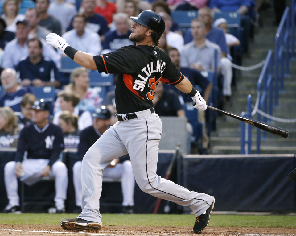 Photo - Miami Marlins' Jarrod Saltalamacchia follows through on a second-inning double in a spring exhibition baseball game against the New York Yankees in Tampa, Fla., Friday, March 28, 2014. The Yankees defeated the Marlins 3-0.(AP Photo/Kathy Willens)
