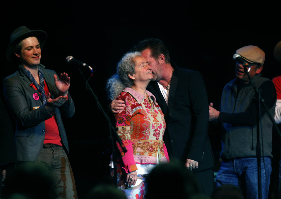 John Mellencamp hugs Woody Guthrie's Daughter Nora Guthrie during the Woody Guthrie Centennial Concert at the Brady Theater Saturday March 10, 2012. At left is Oklahoma musician Taylor Hanson of the group Hanson.  (AP Photo/Christopher Smith, Tulsa World) ORG XMIT: OKTUL107