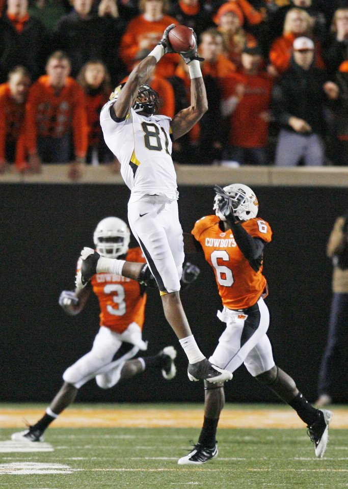 Photo - Tiger Danario Alexander (81) leaps up for a catch in front of Victor Johnson (3) and Andrew McGee (6) during the college football game between Oklahoma State University (OSU) and the University of Missouri (MU) at Boone Pickens Stadium in Stillwater, Okla. Saturday, Oct. 17, 2009.  Photo by Sarah Phipps, The Oklahoman