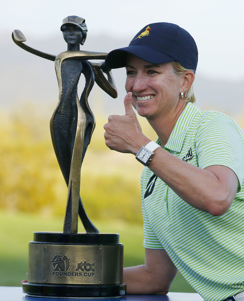 Photo - Karrie Webb, of Australia, gives a thumbs up with the winner's trophy after winning the LPGA Founders Cup golf tournament on Sunday, March 23, 2014, in Phoenix. Webb finished with a one stroke victory and a 19-under par tournament finish. (AP Photo/Ross D. Franklin)