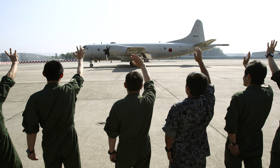 Photo - Ground crew members wave to a Japanese Maritime Defense Force P3C patrol plane as it leaves the Royal Malaysian Air Force base heading for Australia to join a search and rescue operation for the missing Malaysia Airlines, flight MH370, in Subang, Malaysia, Sunday, March 23, 2014. Search planes headed back out to a desolate patch of the southern Indian Ocean on Sunday in hopes of finding answers to the fate of the missing Malaysia Airlines jet, after China released a satellite image showing a large object floating in the search zone. (AP Photo/Lai Seng Sin)