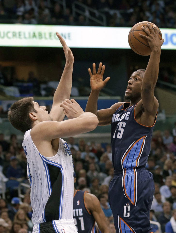 Charlotte Bobcats' Kemba Walker, right, makes a shot over Orlando Magic's Nikola Vucevic during the first half of an NBA basketball game, Friday, Jan. 18, 2013, in Orlando, Fla. (AP Photo/John Raoux)