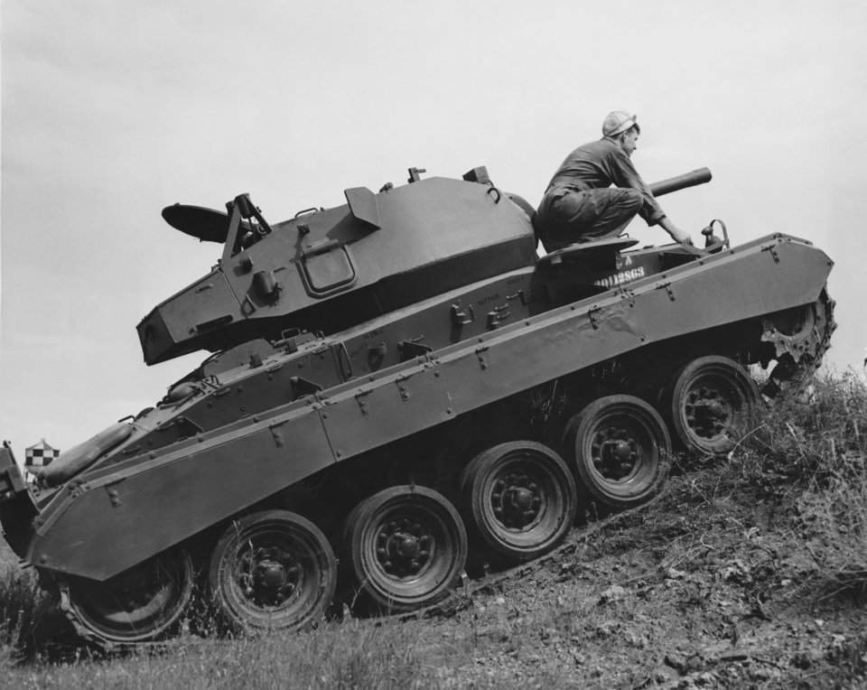"Photo - 45TH INFANTRY / 45TH DIVISION / MILITARY / DEFENSE / SOLDIERS / TANKS / OKLAHOMA:  ""Cpl. Bill Taylor, 700th Ordnance company, 45th division, Lawton, climbs out of the new M-24 light tank which has twin Cadillac engines and hydraulic drive.  It has a top speed of 60 miles an hour.""  Staff photo by Al McLaughlin.  Original dated 07/08/1949.  Published in The Daily Oklahoman 07/10/1949."