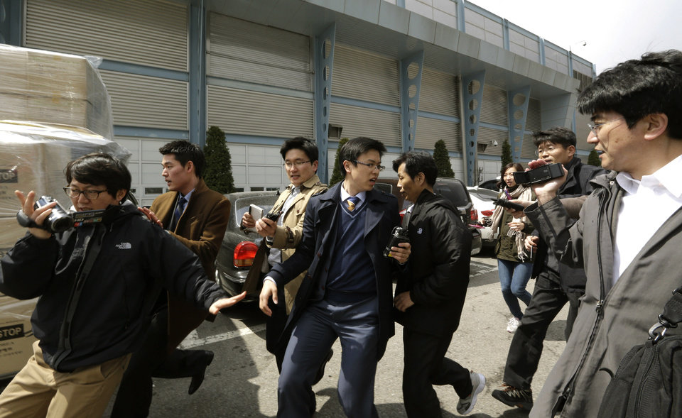 Photo - A South Korean worker, fifth from left, who arrived with boxes of products, seen at left, from North Korea's Kaesong is questioned by media upon his arrival at the customs, immigration and quarantine office near the border village of Panmunjom, which has separated the two Koreas since the Korean War, in Paju, north of Seoul, South Korea, Tuesday, April 9, 2013. North Korean workers didn't show up for work at the Kaesong industrial complex, a jointly run factory complex with South Korea on Tuesday, a day after Pyongyang suspended operations at the last remaining major economic link between rivals locked in an increasingly hostile relationship. (AP Photo/Lee Jin-man)