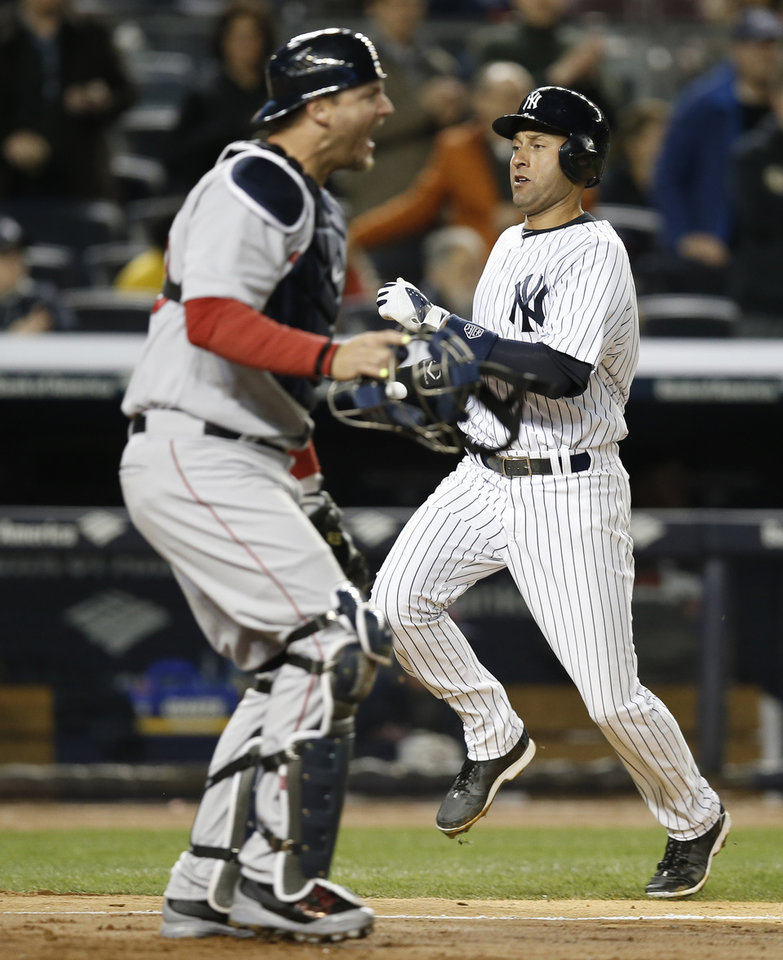 Photo - Boston Red Sox catcher A.J. Pierzynski, left, reacts as New York Yankees' Derek Jeter scores on Jacoby Ellsbury's fifth-inning RBI-single in a baseball game at Yankee Stadium in New York, Thursday, April 10, 2014. The Yankees defeated the Red Sox 4-1. (AP Photo/Kathy Willens)