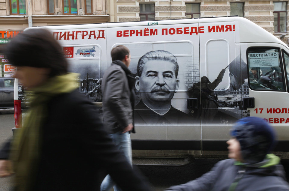 FILE - In this Saturday, Feb. 2, 2013 file photo people walk by a bus adorned with a portrait of Soviet dictator Josef Stalin and a sign reading