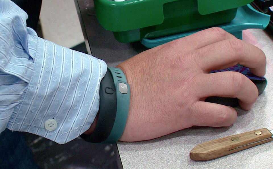Photo - Tim Davis wears his FitBit, green, and Nike FuelBand, black, to track his physical activity and habits. (AP)  Noel Waghorn