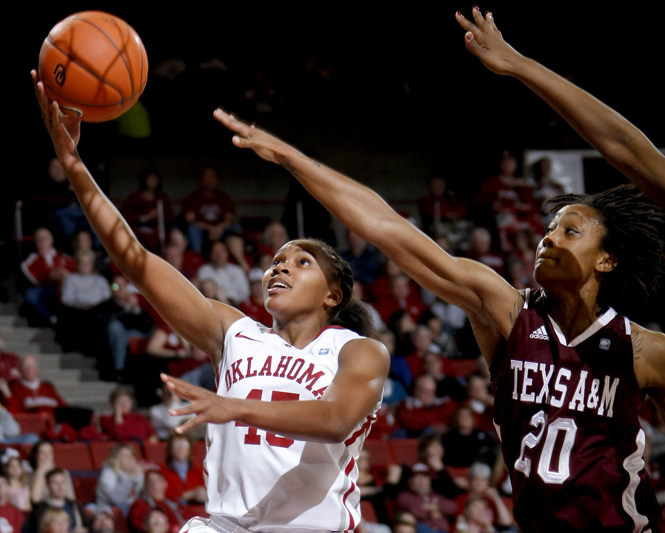 Photo - OU's Jasmine Hartman (45) goes to the basket past Texas A&M's Tyra White (20) during the Big 12 women's basketball game between the University of Oklahoma and Texas A&M at Lloyd Noble Center in Norman, Okla., Wednesday January 26, 2011.  Photo by Bryan Terry, The Oklahoman