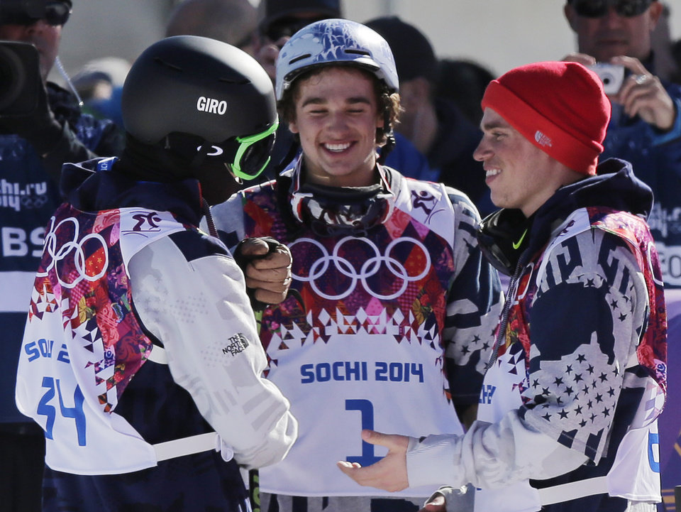 Photo - Men's ski slopestyle gold medal winner Joss Christensen of the United States, left, celebrates with his teammates Gus Kenworthy, right, silver, and Nicholas Goepper, bronze, center,  at the end of Christensen's last run, at the Rosa Khutor Extreme Park, at the 2014 Winter Olympics, Thursday, Feb. 13, 2014, in Krasnaya Polyana, Russia. (AP Photo/Andy Wong)