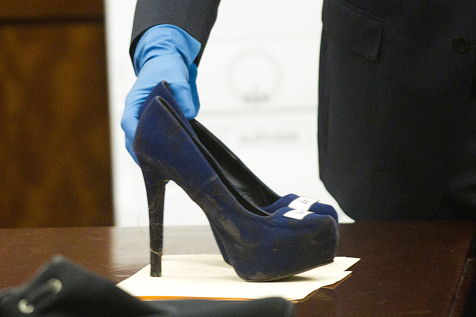Photo - Prosecutor John Jordan sets down a stiletto shoe entered into evidence during the trial against Ana Lilia Trujillo Tuesday, April 1, 2014, in Houston. Trujillo, 45, is charged with murder, accused of killing her 59-year-old boyfriend, Alf Stefan Andersson with the heel of a stiletto shoe, at his Museum District high-rise condominium in June 2013. (AP Photo/Houston Chronicle, Brett Coomer) MANDATORY CREDIT