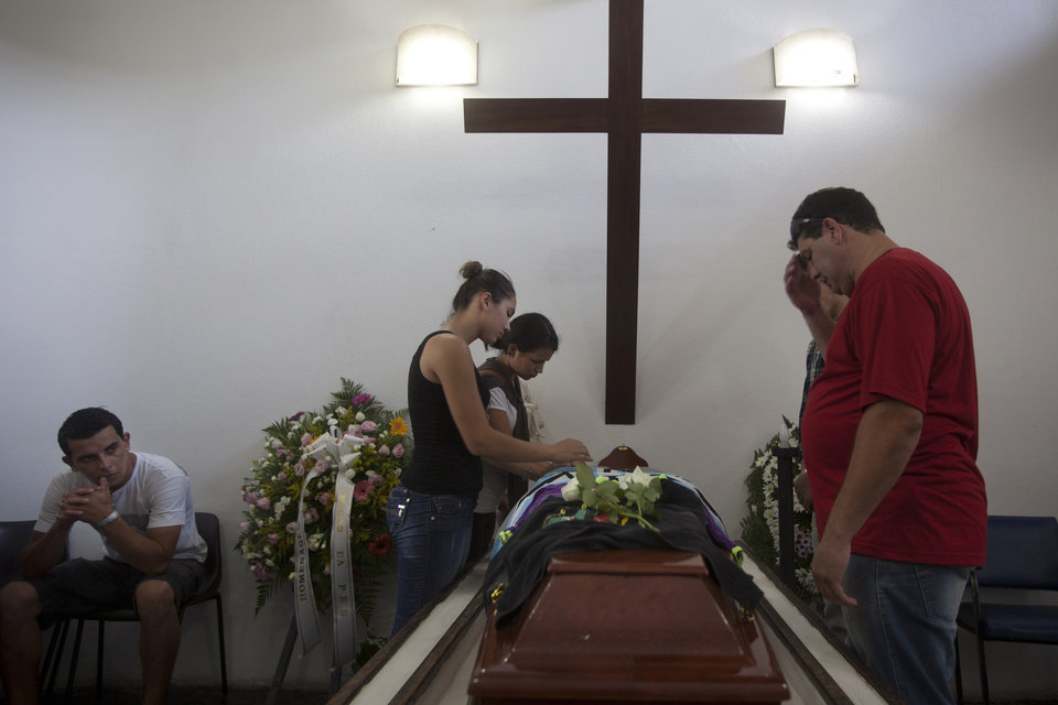 Photo - People attend the funeral of Gustavo Goncalves, the most recent victim of the Kiss nightclub fatal fire, raising the death toll to 235, in Santa Maria, Brazil, Wednesday, Jan. 30, 2013. A fast-moving fire roared through the crowded, windowless nightclub in this southern Brazilian city early Sunday. The first funeral services were held Monday for the victims. Most of the dead were college students 18 to 21 years old. (AP Photo/Felipe Dana)