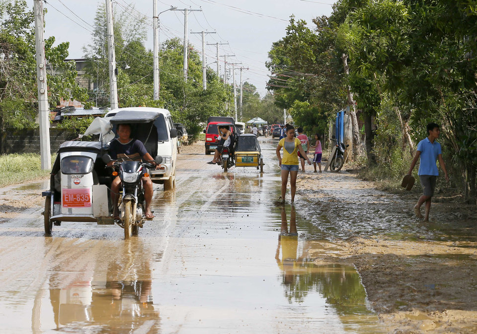 Photo - Residents move through streets full of mud and flood waters in Cabanatuan city, Tuesday, Oct. 20, 2015, two days after Typhoon Koppu (local name