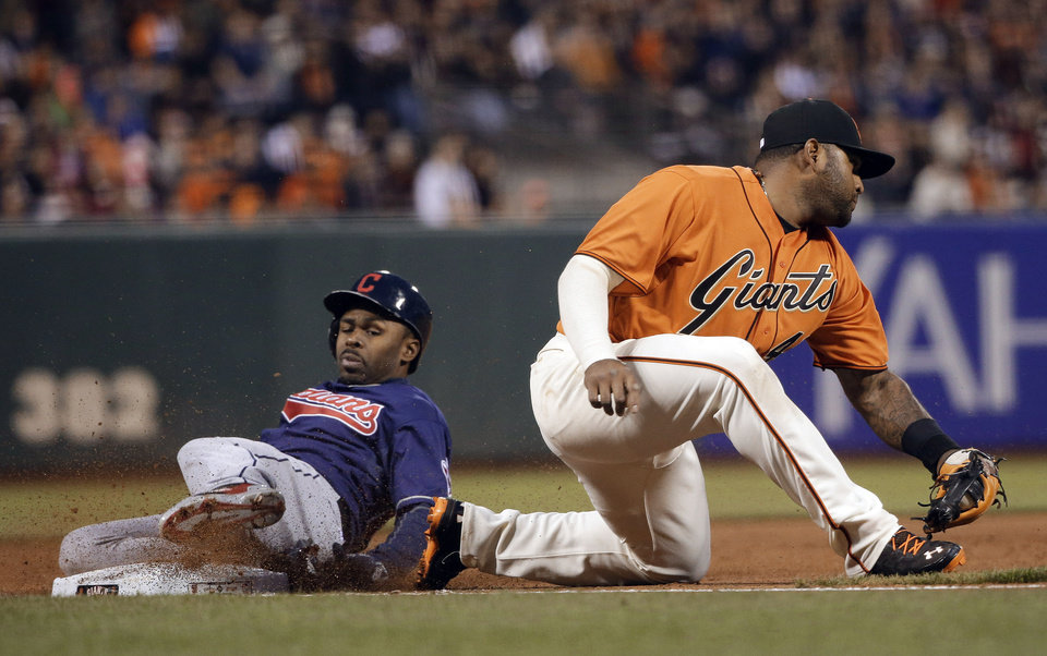 Photo - Cleveland Indians' Michael Bourn, left, slides in safely for a triple next to San Francisco Giants third baseman Pablo Sandoval during the third inning of a baseball game Friday, April 25, 2014, in San Francisco. (AP Photo/Marcio Jose Sanchez)