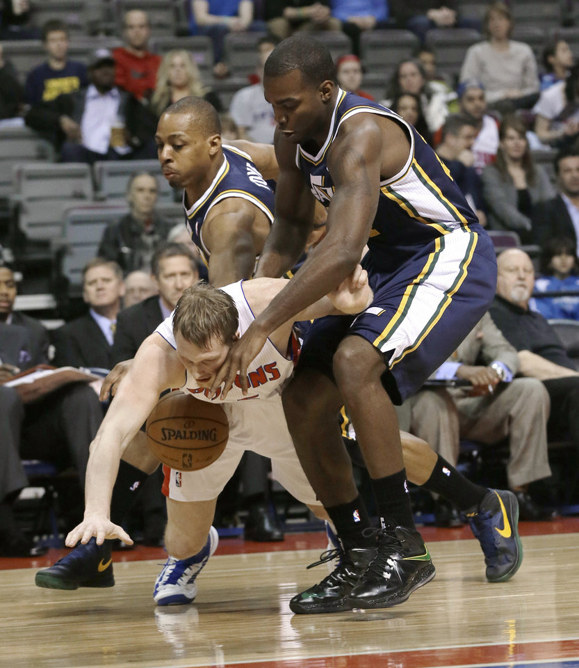 Photo - Utah Jazz forward Paul Millsap, right, and guard Randy Foye, left, crowd Detroit Pistons forward Kyle Singler during the first quarter of an NBA basketball game at the Palace of Auburn Hills, Mich., Saturday, Jan. 12, 2013. (AP Photo/Carlos Osorio)