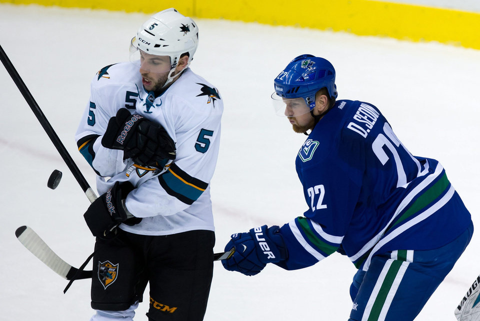 San Jose Sharks' Jason Demers, left, is hit by a shot as Vancouver Canucks' Daniel Sedin, of Sweden, watches during second period NHL hockey action in Vancouver, British Columbia, on Thursday Nov. 14, 2013. (AP Photo/The Canadian Press, Darryl Dyck)