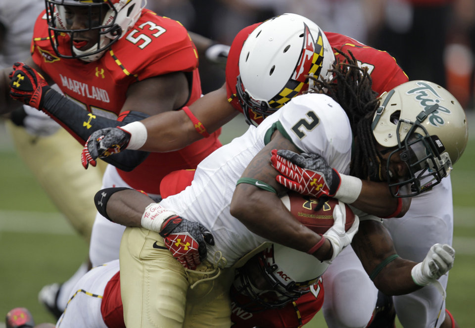 Photo -   William & Mary's B.W. Webb (2) is tackled by Maryland's back Eric Franklin, top, and Sean Davis (21), bottom, as Maryland's L.A. Goree (53) defends during a punt return in the third quarter of a NCAA college football game, Saturday, Sept. 1, 2012, in College Park, Md. Maryland won 7-6. (AP Photo/Luis M. Alvarez)