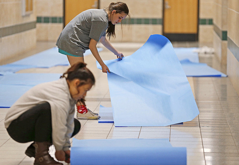 Edmond Santa Fe High School seniors Rachel Deutsch, 17, top, and  Jenney Huynh, 18, unroll paper to cover the walls for Double Wolf Dare Week.