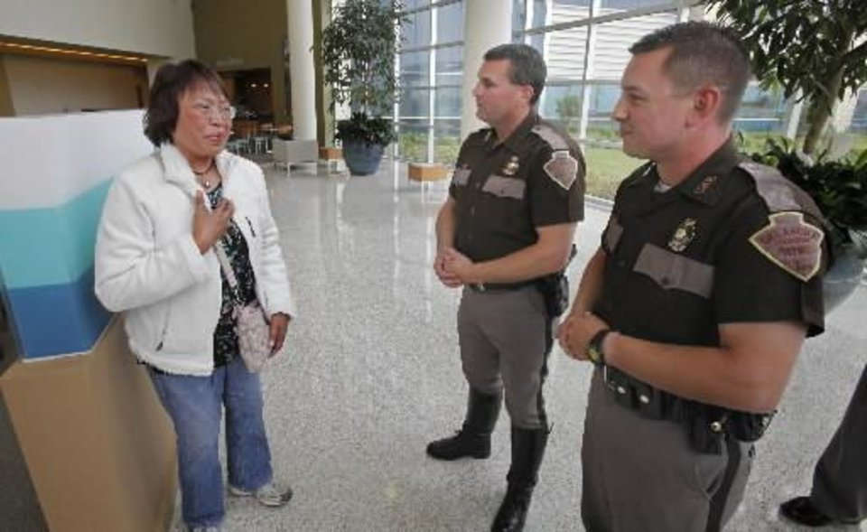 Nenita Mijares thanks Highway Patrol Troopers Steve Johnson (center) and Ken Pittman at the Norman Regional Healthplex on Thursday, April 21, 2011, in Norman, Okla. The troopers performed CPR on her husband Hector Mijares, a retired commercial airline pilot, while working a multi-vehicle accident at Interstate 35 and 27th Street in Moore, OK. The couple are living in Oklahoma City after retiring in the Philippines. Photo by Steve Sisney, The Oklahoman
