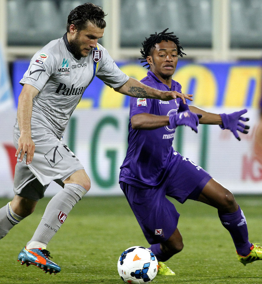 Photo - Fiorentina's Juan Cuadrado, right, is challenged by Chievo's Perparim Hetemaj during a Serie A soccer match between Fiorentina and Chievo Verona, at the Artemio Franchi stadium in Florence, Italy, Sunday March 16, 2014. (AP Photo/Fabrizio Giovannozzi)