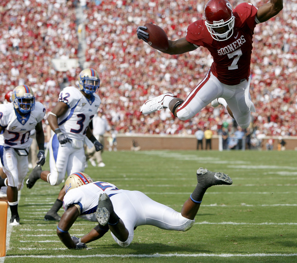 OU's DeMarco Murray leaps over Tulsa's DeAundre Brown for a touchdown during the first half of the college football game between The University of Oklahoma Sooners (OU) and the University of Tulsa Golden Hurricane (TU) at the Gaylord Family -- Oklahoma Memorial Stadium on Saturday, Sept. 19, 2009, in Norman, Okla.   Photo by Bryan Terry, The Oklahoman. ORG XMIT: KOD