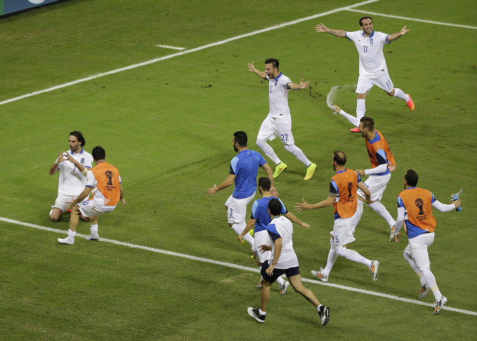 Photo - Greece's Giorgos Samaras, far left, celebrates with his team after he scored on a penalty kick in the final minutes during the group C World Cup soccer match between Greece and Ivory Coast at the Arena Castelao in Fortaleza, Brazil, Tuesday, June 24, 2014. Greece beat Ivory Coast 2-1. (AP Photo/Sergei Grits)