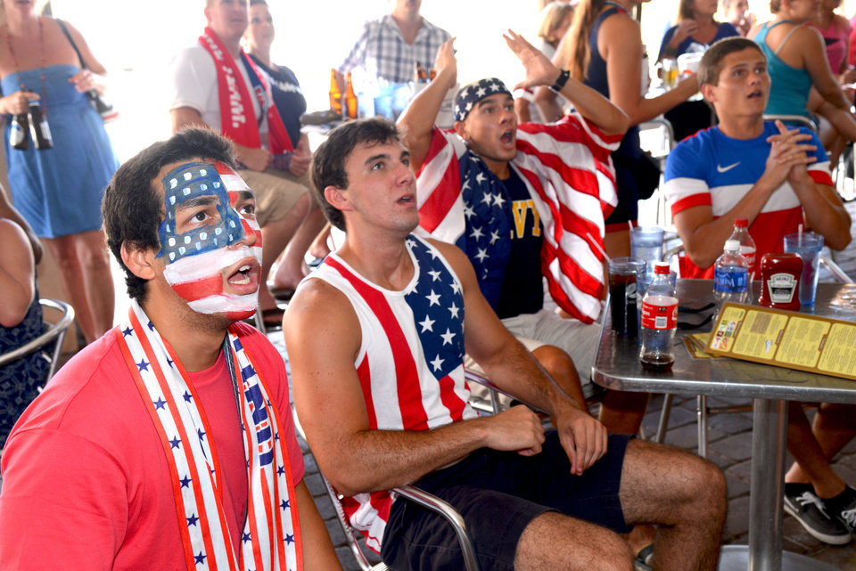 Photo - Jose Rodriguez, from left, Mark Dickinson, Luke Cantin, and Christian react to play early in a World Cup soccer match between the United States and Belgium, Tuesday, July 1, 2014, in Jacksonville Beach, Fla. (AP Photo/The Florida Times-Union, Bob Mack)