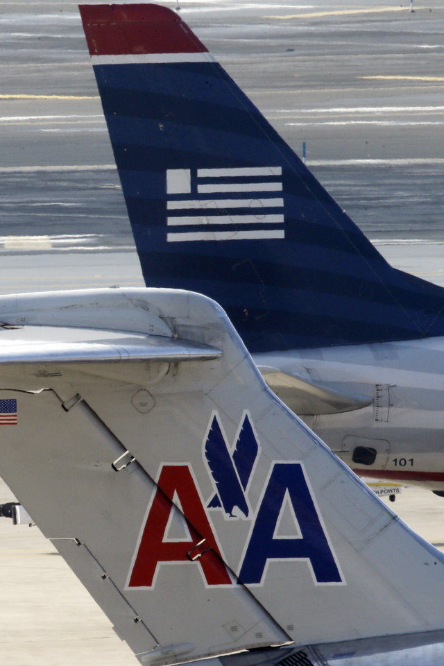 American Airlines and US Airways jets park at gate at the Philadelphia International Airport, Thursday, Feb. 14, 2013, in Philadelphia. The merger of US Airways and American Airlines has given birth to a mega airline with more passengers than any other in the world. ( (AP Photo/Matt Rourke)