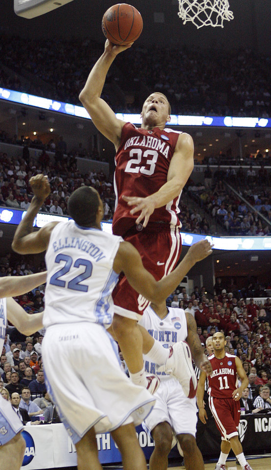 Photo - Oklahoma's Blake Griffin (23) goes over North Carolina's Wayne Ellington (22) for a dunk during the first half in the Elite Eight game of NCAA Men's Basketball Regional between the University of North Carolina and the University of Oklahoma at the FedEx Forum on Sunday, March 29, 2009, in Memphis, Tenn.