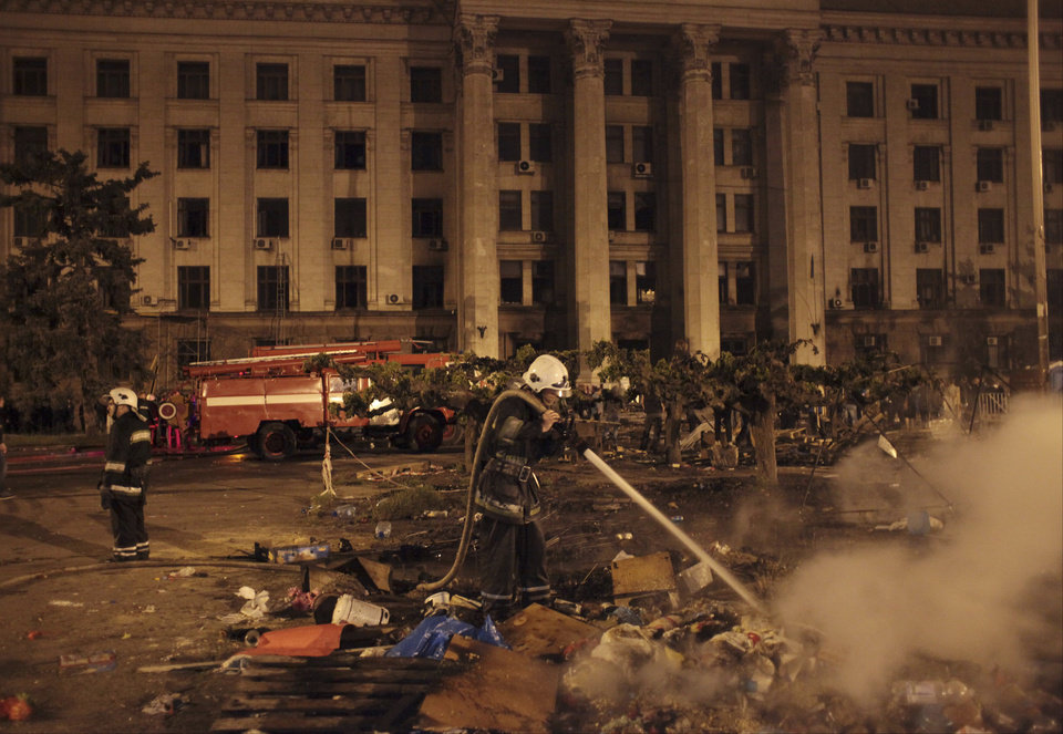 Photo - A firefighter puts off burning rubbish outside the burnt trade union building where more than 30 people died trying to escape during clashes in Odessa, Ukraine, on Friday, May 2, 2014. Odessa had been largely tranquil since the February toppling of President Viktor Yanukovych, who fled to Russia. But clashes erupted Friday between pro-Russians and government supporters in the key port on the Black Sea coast, located 550 kilometers (330 miles) from the turmoil in the east. (AP Photo/Sergei Poliakov)