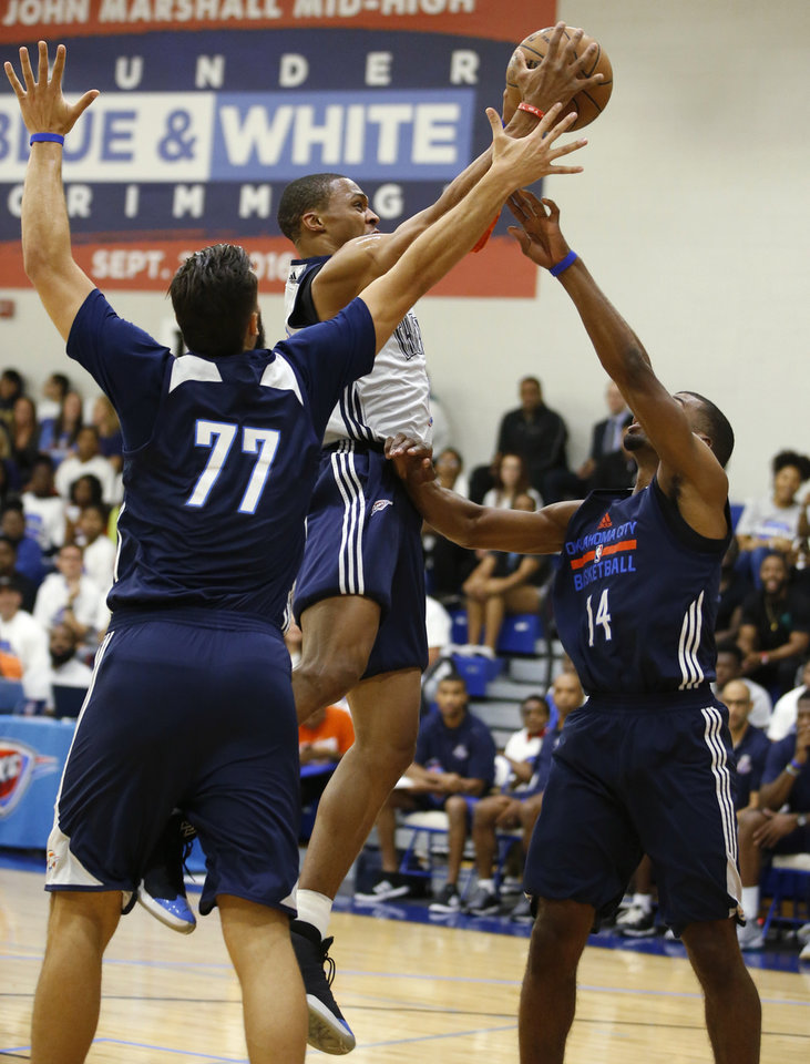 Photo - Oklahoma CIty's Russell Westbrook goes between Joffrey Lauvergne, left, and Josh Huestis during the Thunder's annual Blue and White Scrimmage at John Marshall Mid-High School in Oklahoma City, Tuesday, Sept. 27, 2016. Photo by Bryan Terry, The Oklahoman