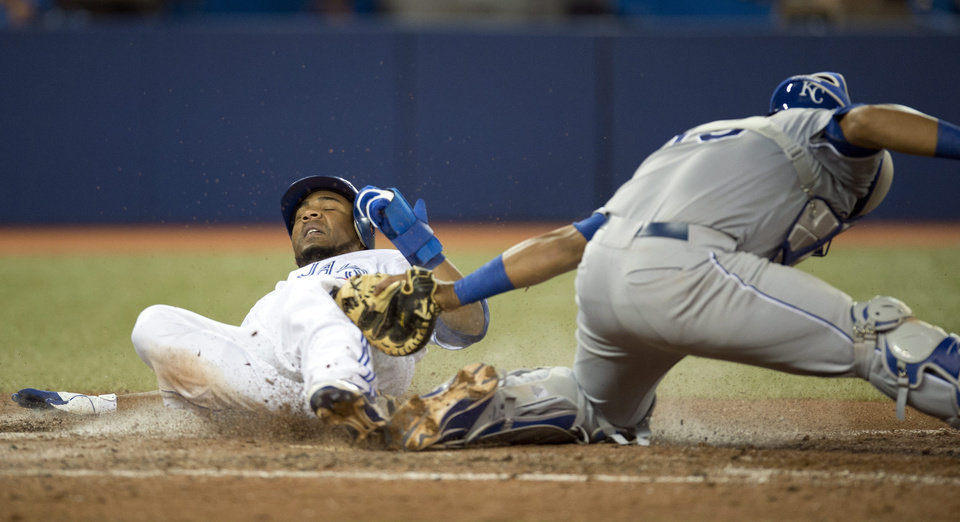 Photo -   Toronto Blue Jays Edwin Encarnacion scores past the tag of Kansas City Royals catcher Salvador Perez during the eighth inning of a baseball game in Toronto on Thursday, July 5, 2012. (AP Photo/The Canadian Press, Frank Gunn)