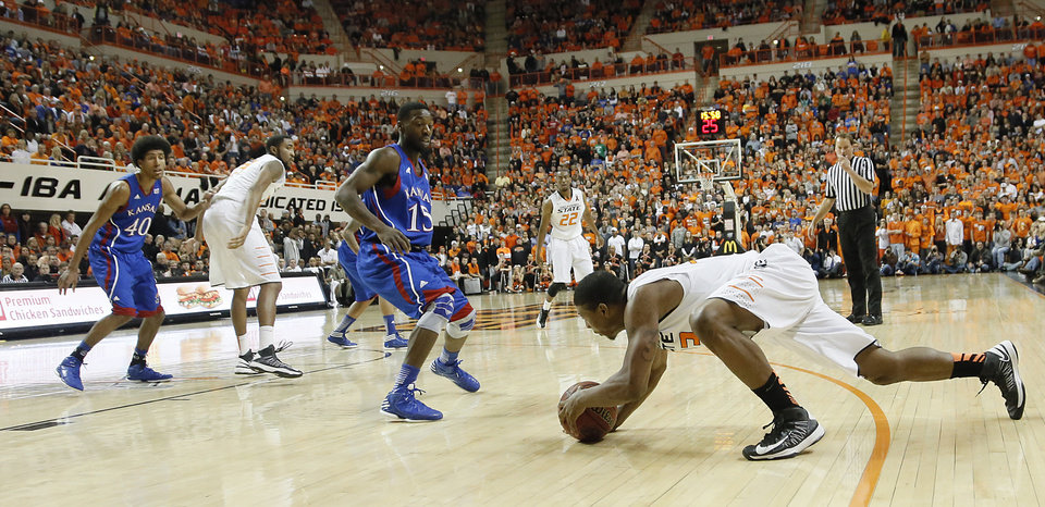 Photo - Oklahoma State 's Marcus Smart (33) slips as he starts to drive on Kansas' Elijah Johnson (15) during the college basketball game between the Oklahoma State University Cowboys (OSU) and the University of Kanas Jayhawks (KU) at Gallagher-Iba Arena on Wednesday, Feb. 20, 2013, in Stillwater, Okla. Photo by Chris Landsberger, The Oklahoman