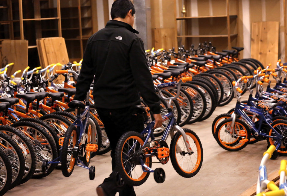 A volunteer carries two small bikes equipped with training wheels to an area where assembled bikes are kept. More than 150 volunteers donated their time and skills Saturday morning, Dec. 1, 2012, assembling 830 childrens\' bicycles for the Salvation Army\'s bike giveaway project. The bicycles will be distributed to children in need at Christmas. Bikes were assembled inside the former J.C. Penney store in the vacant Crossroads Mall. Photo by Jim Beckel, The Oklahoman