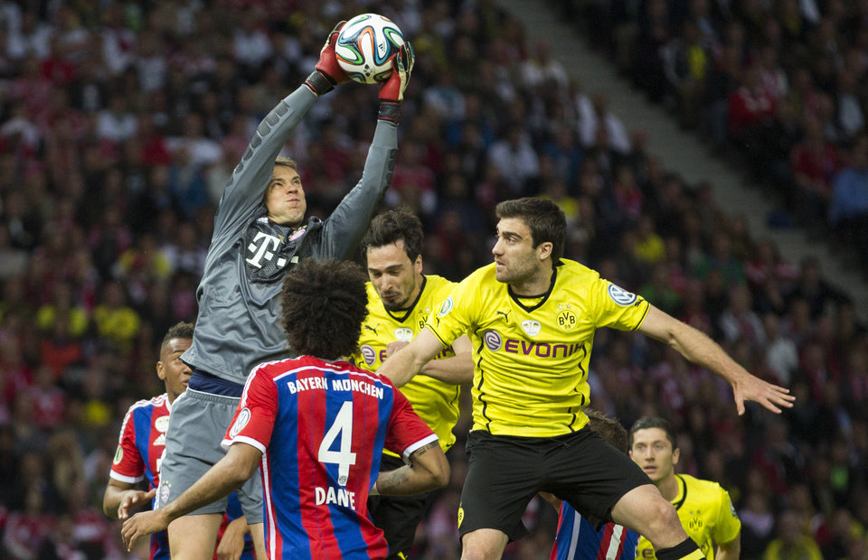 Photo - Bayern goalkeeper Manuel Neuer, left, makes a save against Dortmund's Sokratis of Greece, right, and Dortmund's Mats Hummels, background, during the German Soccer Cup Final between FC Bayern Munich and Borussia Dortmund at the Olympic Stadium in Berlin, Germany, Saturday, May 17, 2014. (AP Photo/Gero Breloer)