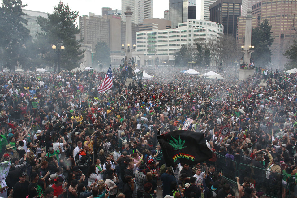 Photo - Members of a crowd numbering tens of thousands smoke marijuana simultaneously at 4:20 PM, at the Denver 420 pro-marijuana rally at Civic Center Park in Denver on Saturday, April 20, 2013. Even before the passage in November 2012 of Colorado Amendment 64 promised the legalization of marijuana for recreational use, April 20th has for years been a celebration of marijuana counterculture, and the 2013 rally draw larger crowds than previous years. (AP Photo/Brennan Linsley)