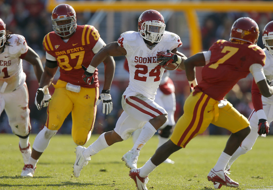 Photo - Oklahoma's Brennan Clay (24) runs pas Iowa State's David Irving (87) during a college football game between the University of Oklahoma (OU) and Iowa State University (ISU) at Jack Trice Stadium in Ames, Iowa, Saturday, Nov. 3, 2012. Oklahoma won 35-20. Photo by Bryan Terry, The Oklahoman