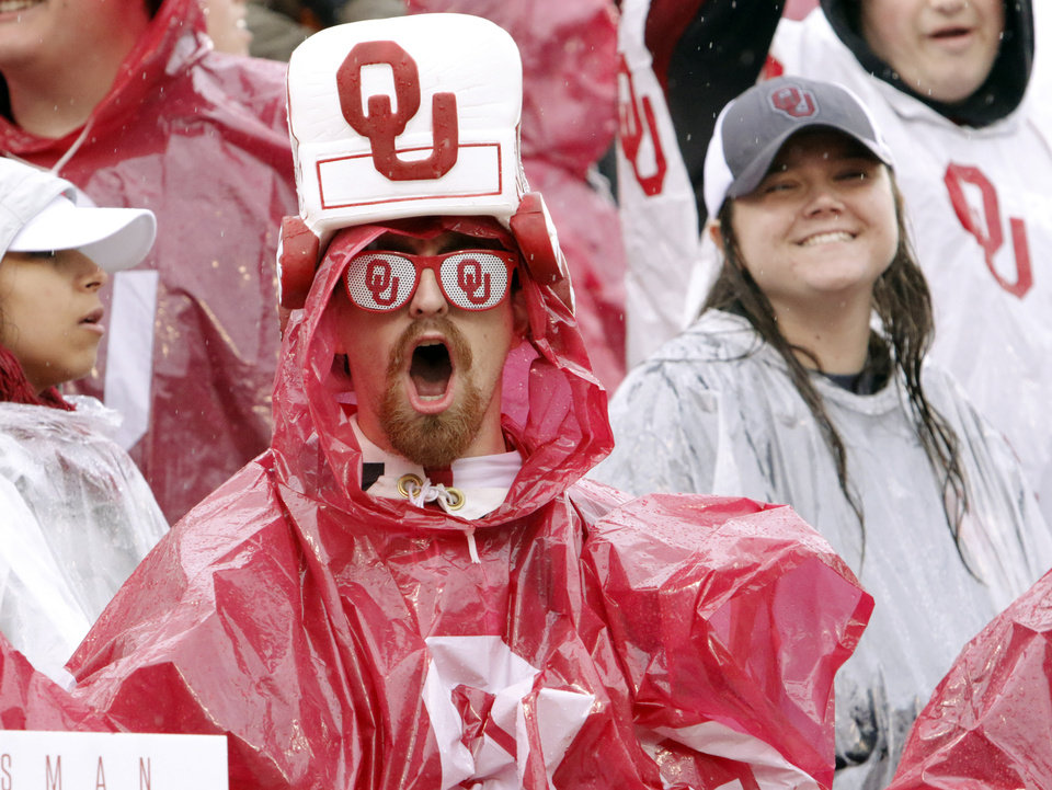 Photo - Ryan Hamilton, Claremore Senior, wears his rain and Sooner gear during the Bedlam college football game between the Oklahoma Sooners (OU) and the Oklahoma State Cowboys (OSU) at Gaylord Family - Oklahoma Memorial Stadium in Norman, Okla., Saturday, Dec. 3, 2016. Photo by Steve Sisney, The Oklahoman