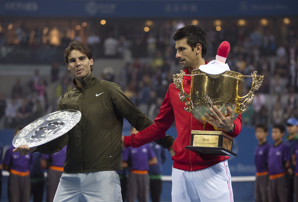 Rafael Nadal of Spain, left, leaves a photo call, as Novak Djokovic of Serbia holds the trophy after the final of the China Open tennis tournament at the National Tennis Stadium in Beijing, China Sunday, Oct. 6, 2013. Djokovic defeated Nadal 6-3, 6-4. (AP Photo/Andy Wong)