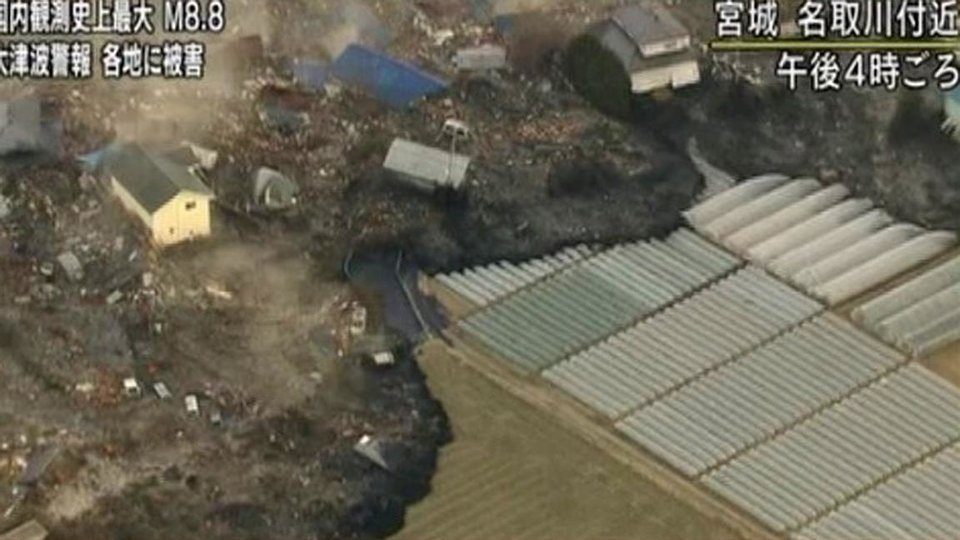 Photo - In this video image taken from Japan's NHK TV, a tsunami surge carrying debris sweeps between houses to reach poly tunnels on farmland near Sendai in Miyagi Prefecture Japan Friday March 11, 2011 following a massive earth quake. A magnitude 8.9 earthquake slammed Japan's northeastern coast Friday, unleashing a 13-foot (4-meter) tsunami that swept boats, cars, buildings and tons of debris miles inland. Fires triggered by the quake burned out of control up and down the coast.  (AP PHOTO/NHK TV) MANDATORY CREDIT, JAPAN OUT, TV OUT,  NO SALES, EDITORIAL USE ONLY ORG XMIT: LON833
