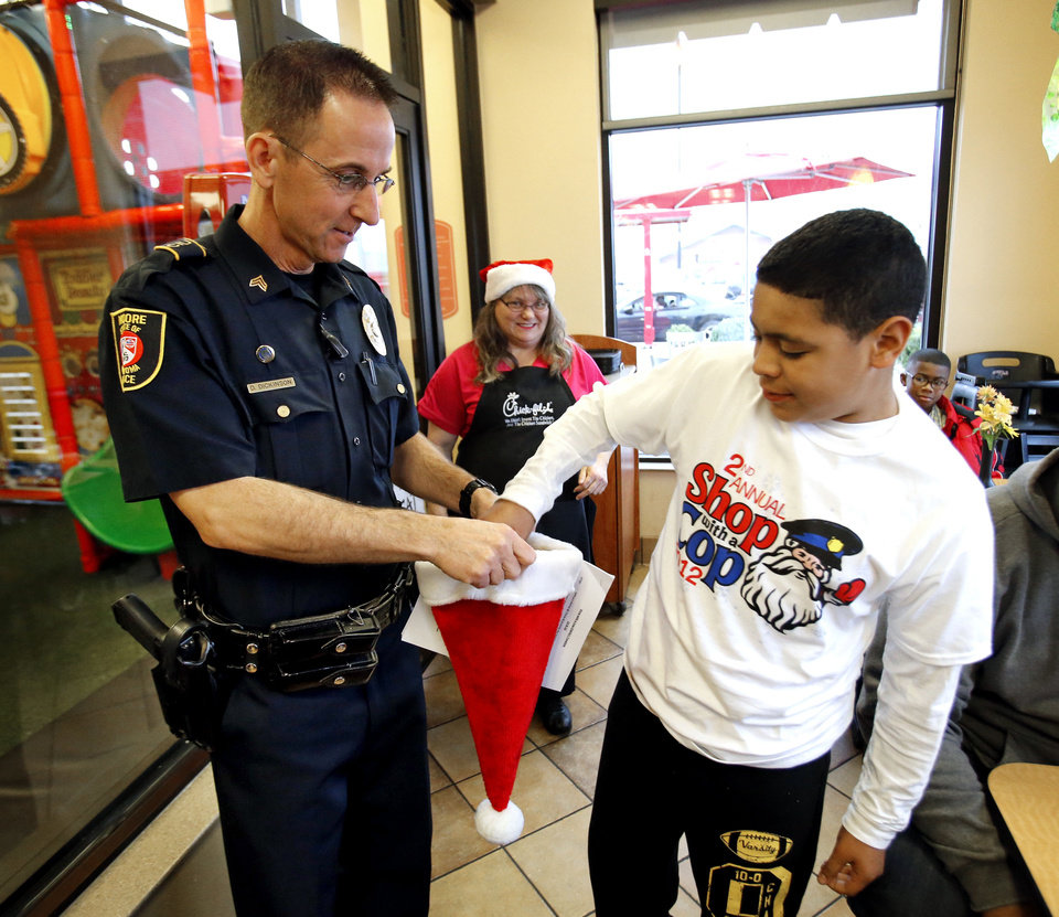 "Camdyn Braden, 10, draws the badge number of his escort from a hat held by David Dickinson during  ""Shop With a Cop"" on Saturday in Moore. Photo by Steve Sisney, The Oklahoman <strong>STEVE SISNEY - THE OKLAHOMAN</strong>"